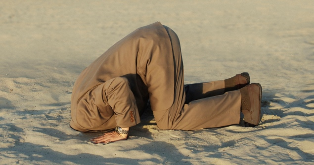 man in suit with his head in the sand