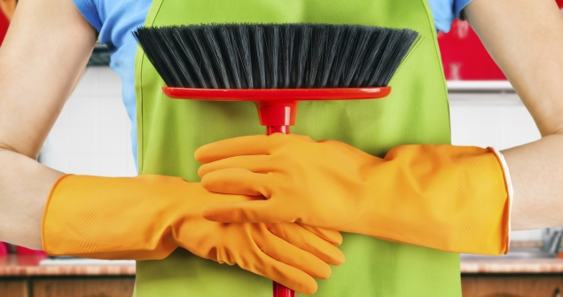 person with cleaning gloves holding a broom