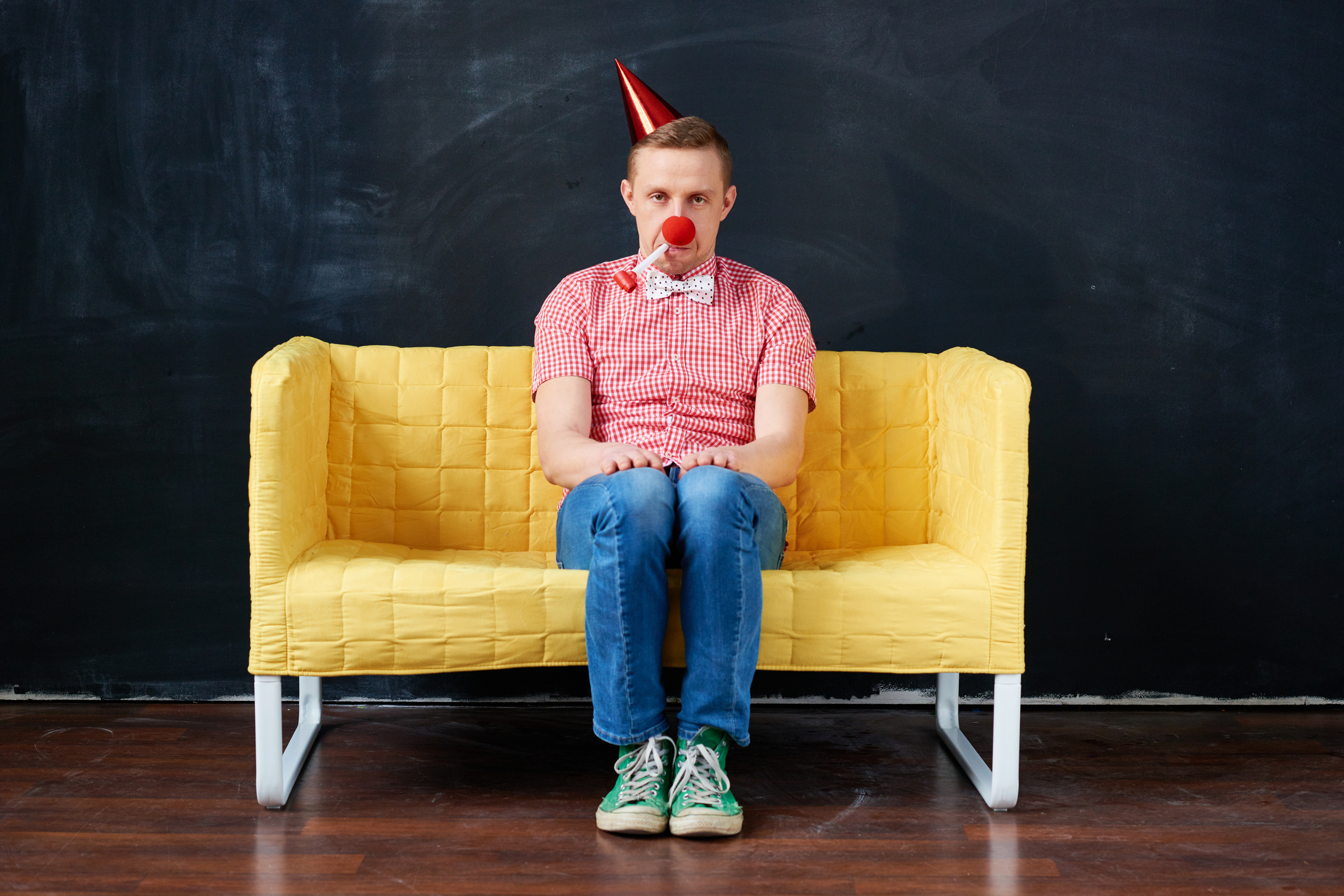 Young man sitting with party blower and party hat on sofa