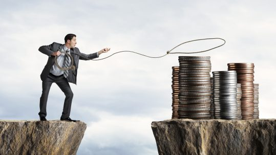 Businessman Attempting To Lasso A Stack Of Coins