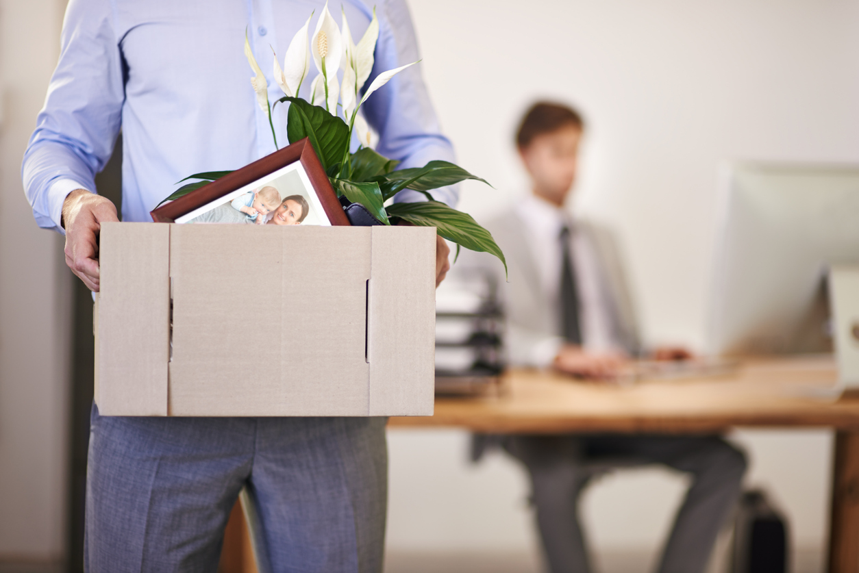 Man quitting his job, and carrying a box of personal items.