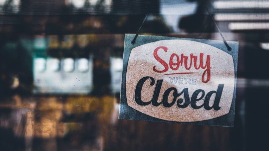 "A sign on a window saying ""sorry, closed""."