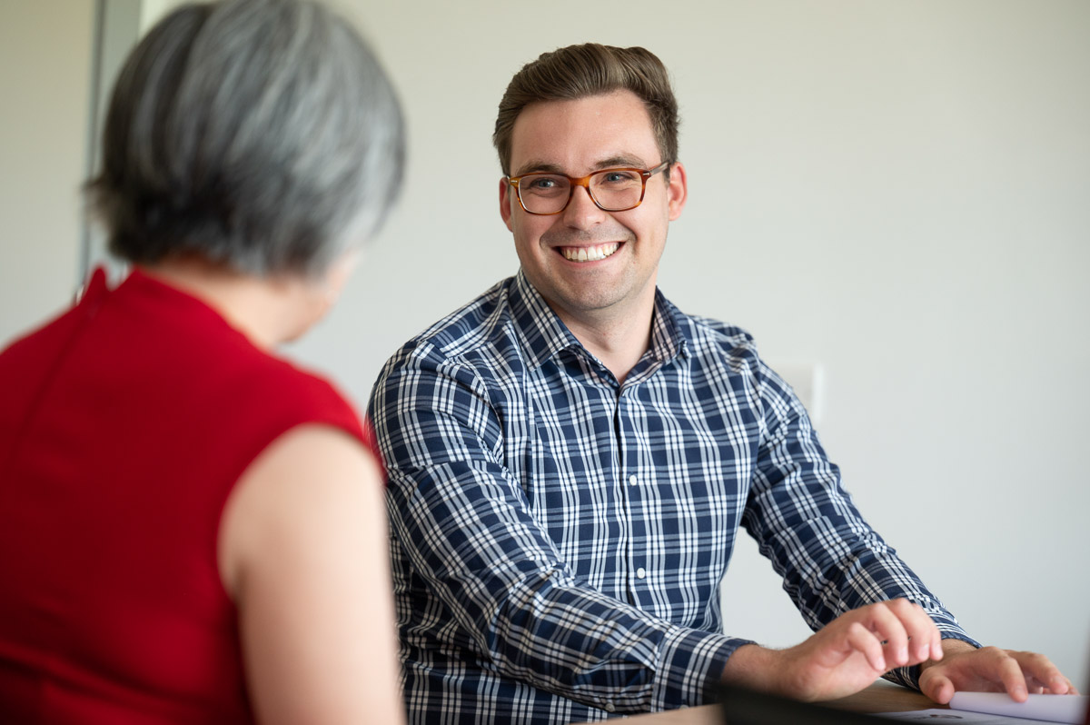 Two people in a meeting, with one person smiling at his client.